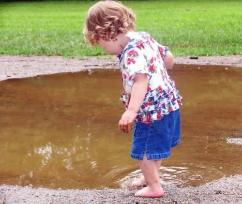 Девочка играет в луже