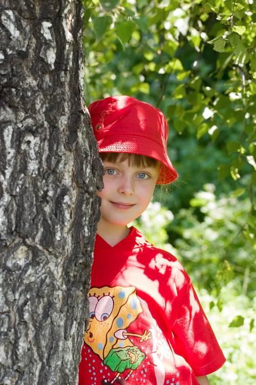 Девочка прячется за деревом
