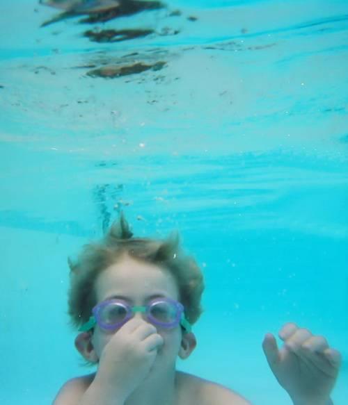 Мальчик учится плавать